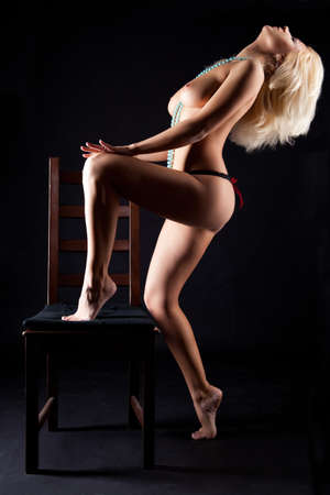 young naked blonde women with chair on black background Stock Photo - 9677159