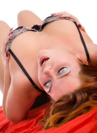 young beauty sensual woman lying on red fabric
