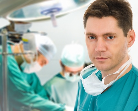 Male surgeon with two doctors on background in operation room Stock Photo - 9640368