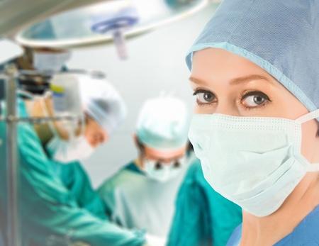 guanti infermiera: dottoressa con team chirurgico sullo sfondo Archivio Fotografico