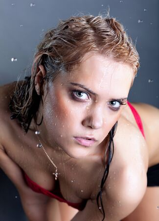 young wet beautiful sensual blonde woman at black background photo