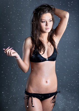 young woman with water droplets falling at black bacground photo