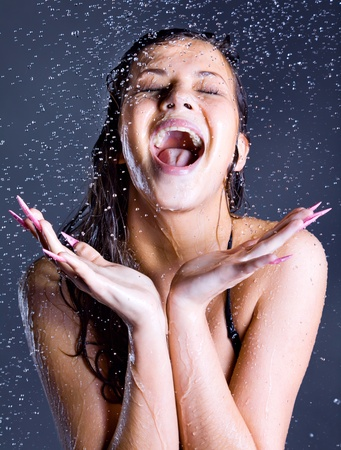 young expressive ecstatic screaming beauty woman with falling water droplets  Stock Photo