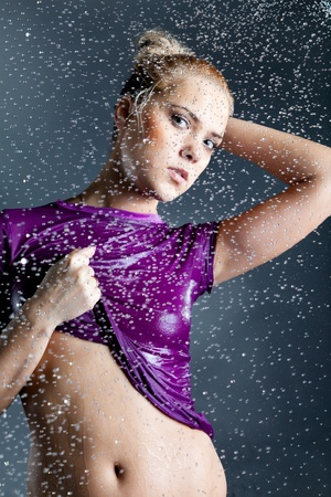 young blonde woman with water droplets falling at black background photo