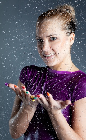 young smiley blonde woman with falling water droplets at black background photo