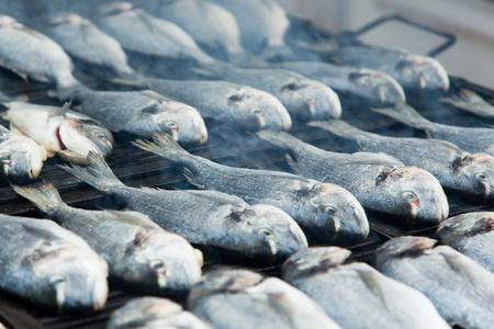 sardinas: pescado a la parrilla con humo. imagen con dof bajo.
