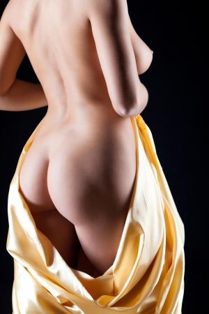 naked woman back: Junge nackte schlanke Frauen mit einem Tuch auf schwarzem Hintergrund