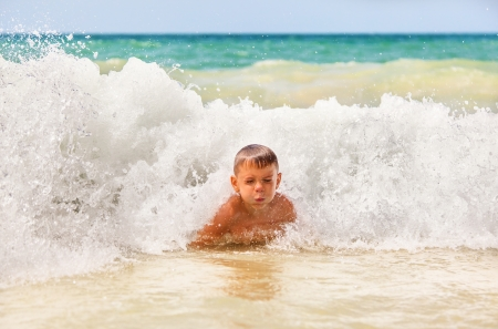 boy in the waves breaking on the shore of beach