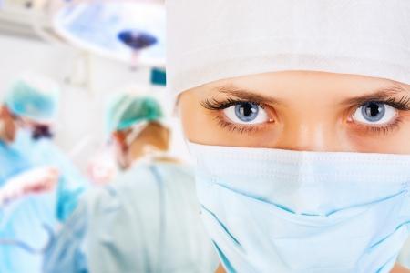 enfermera con cofia: Primer plano de un cirujano femenino con su equipo en la sala de operaciones