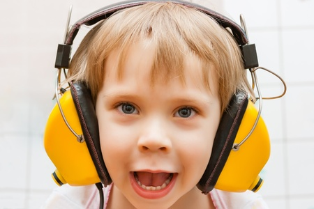 Little boy with headphones listening to music photo