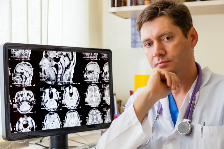 doctor office: Doctor with an MRI scan of the Brain on Monitior Stock Photo