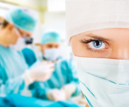 general practitioner: Close-up of a female surgeon with his team in operation room Stock Photo