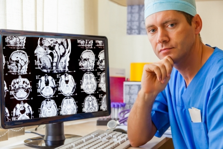 mri: Experienced doctor with an MRI scan of the Brain on Monitior Stock Photo