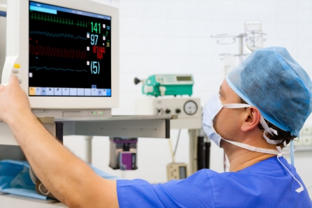Male anaesthesiologist at monitor in operation room