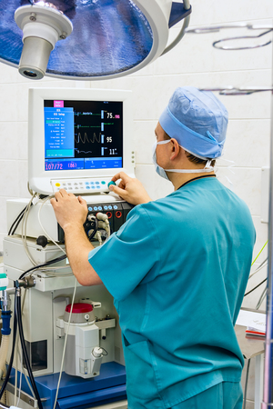 Anaesthesiologist with monitor in operation room