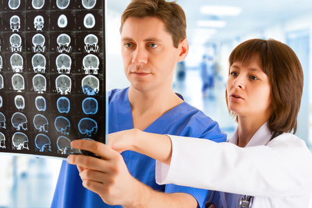tomogram: Male and female doctors looking at tomogram in hospitals corridor Stock Photo