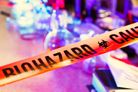 Caution tape in hazardous biochemicals laboratory with equipment photo