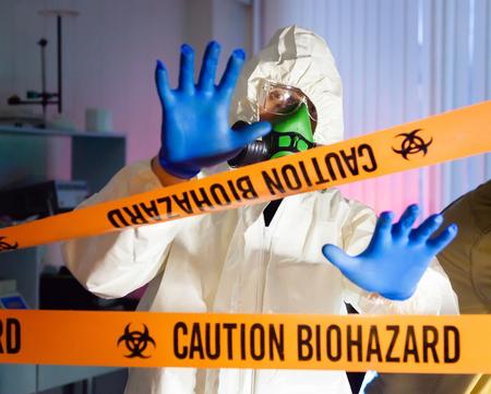 Scientist behind caution tape in hazardous biochemicals laboratory  photo