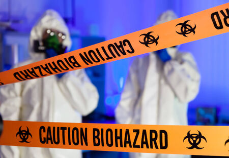 Two scientists behind caution tape in hazardous biochemicals laboratory  photo