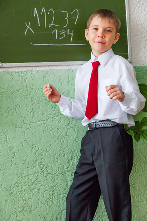Smiling schoolboy at blackboard with chalk photo