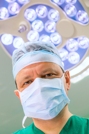 Mature surgeon in operation room with lamp on background