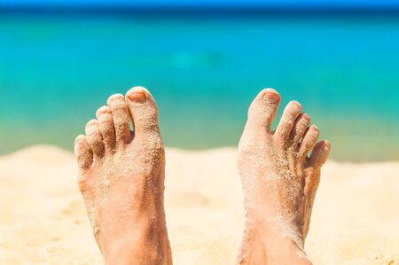 feet relaxing: Relaxing on a beach. Feet with tha sand.
