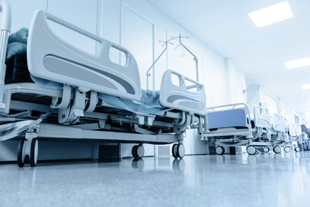 healthcare professional: long corridor in hospital with surgical beds. tinted picture