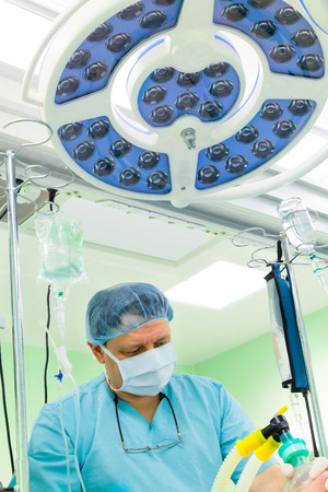 anesthetist: Anesthesiologist working in operation room under lamp