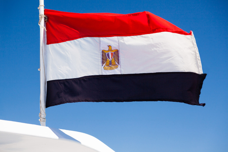egypt flag: Bandera egipcia ondulado sobre fondo azul Foto de archivo