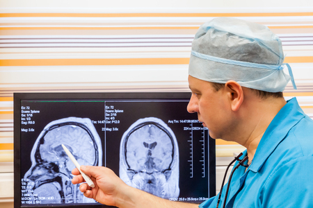Doctor examining an MRI scan of the Brain on Monitior photo