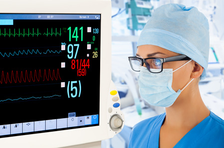 surgical mask woman: Female doctor with monitor in intensive care unit. Stock Photo