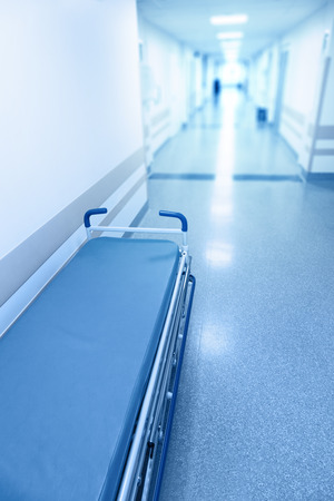 gurney: Long corridor in hospital with surgical gurney. Tinted picture Stock Photo