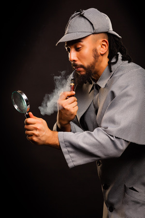 sherlock: man with pipe and magnifying glass on black background Stock Photo