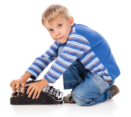 Playful Little Boy with Old Typewriter Stock Photo