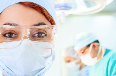 Young female doctor in operation room with her team on background photo