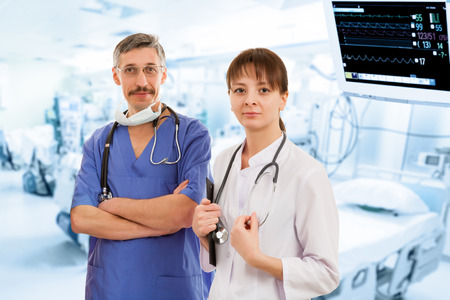 Two Doctors in Hospital with Monitor on Background photo