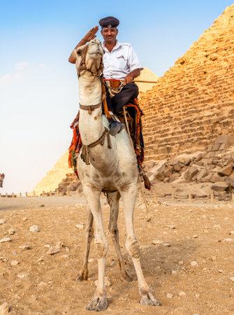 EGYPT, GIZA - OCTOBER 29 2014: A Man in Police Uniform Riding a Camel near the Giza Pyramids
