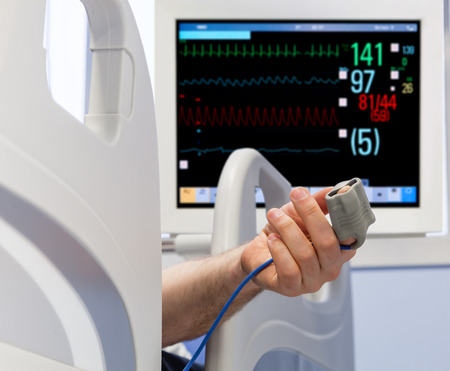PULSE: Patients Hand in Bed with Oximeter and Monitor on Background