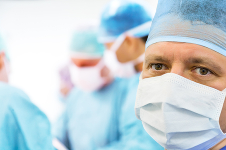 Glance of the mature surgeon in the operating room 免版税图像