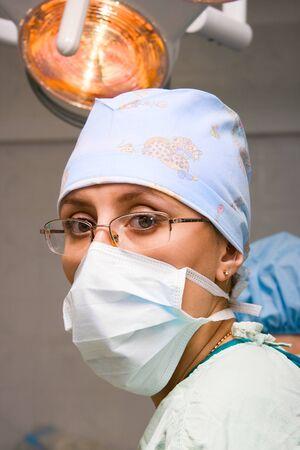 Cirujano de sexo femenino joven con máscara debajo de la lámpara en la sala de operaciones