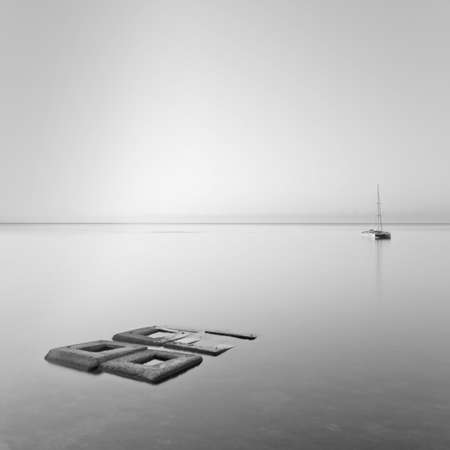 Black   White minimalist seascape with rocks   ship