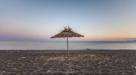 Straw umbrella on the beach in a minimalist seascape Stock Photo