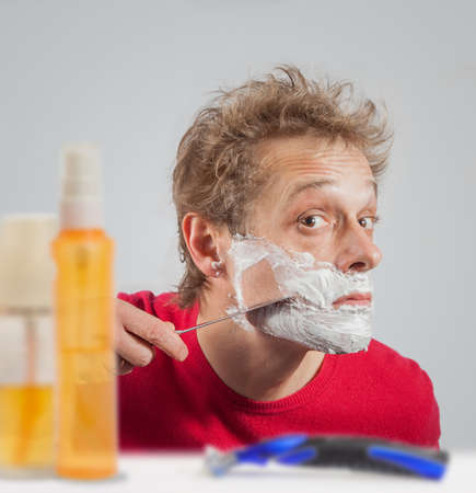 Man with shaving cream to his face Stock Photo