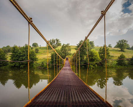 Metal suspension bridge over the river
