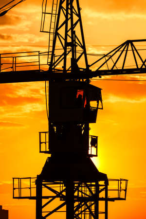 Industrial construction crane silhouette over sun at sunrise Stock Photo