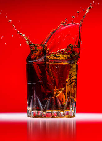 Glass with whiskey splash on red background Stock Photo