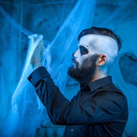 Halloween concept with young man in day of the dead mask face art photo