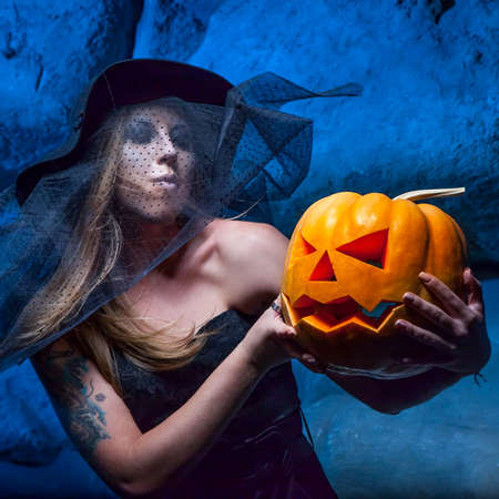 Halloween concept with young witch woman