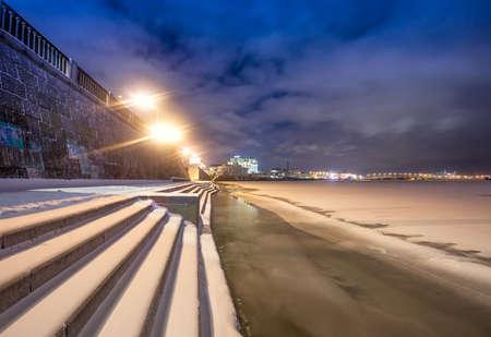 Winter embankment in city at night
