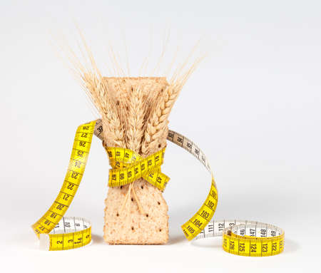 A yellow measuring tape wrapping wheat cracker or crispbread - healthy eating concept Stock Photo
